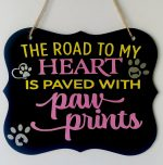 black sign with a quotes for pets in yellow and pink on it
